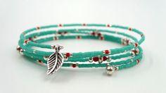 Bracelet mémoire à cinq tours en perles de rocaille Miyuki Delicas turquoises, rouges et argentées, terminé par deux petites breloques de métal argentées. Disponible à l'achat en me laissant …