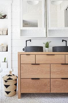 Stone vessel sink on oak vanity in rustic farmhouse bathroom by Trinette Reed for Stocksy United