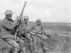 Battle of Epehy. Three soldiers resting on ground near Epehy captured by the…