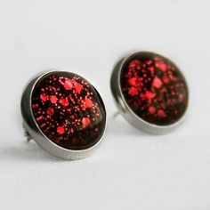 Red glittery stud earrings. These post earrings have mixed small and hexagonal glitter. Lovingly hand painted 12mm glass set in a silver