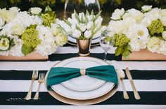 Bold napkin gathered into napkin ring, tucked under uppermost plates to resemble a bow.