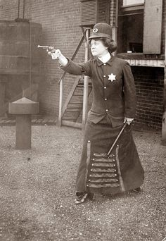 This photo is from the 1920's & shows a police woman with a Billy Club & packing a pistol.