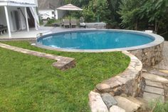 Freedom above ground pool installed partially above ground with partial wood deck and stone surround.