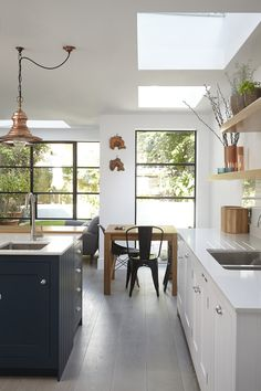 Modern contemporary kitchen with wall of windows and sky light.  By Blakes London