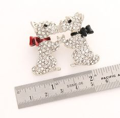 Schnauzer dogs brooch. This beautiful and unique schnauzer broach pin jewelry piece in antique silver tone setting is encrusted with sparkling faux diamond crystals and is the perfect gift idea or would make a unique and one of a kind compliment to any ensemble. Measures 1 3/4W x 1 1/2H  This two dogs broach can be added to your bridal brooch bouquet, purse, photo album etc. for additional style and decor. Make a magnet for refrigerator, desk, etc. by attaching a magnet to the back. By…