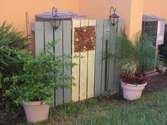 privacy fence for an HVAC unit (or trash cans, etc) made from wood shipping pallets, painted and decorated.