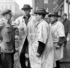 Bela Zola Life in the Mirror Series. Three fish porter wearing their distintive hats at Billingsgate Fish Market in the East End of London discussing trade. 28th February 1954.
