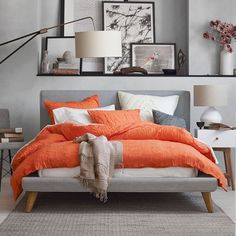 Grey upholstered bed with tangerine bedding