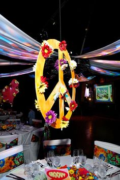 Suspended Peace Signs centerpieces adorned with flowers for 60's inspired celebration. Decor by Mark Rupard of Elizabeth House: