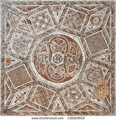 Fragment of an ancient  floor mosaic. Colorful small tiles, unusual geometric ornament, floral and regular forms. Roman fortress. Israel