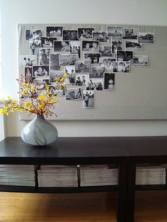 linen covered canvas, black and white photos pinned to it