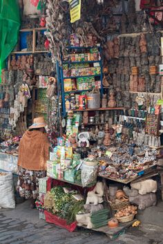 """Part of the City  street market in LaPaz. A woman is selling objects used by the people to give payments of thanks  to Pacha Mama, Mother Earth, and objects used by curendaros (healers). Some are herbs we may discover and use in our medicines some day. Tourists who don't know what they are looking at or who don't understand the culture call this """"the witch's market."""""""
