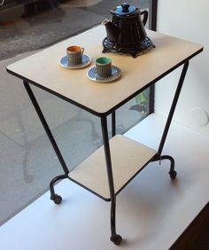 rullapöytä / sivupöytä / / tarjoilupöytä / TV-taso 50 luvulta Ranskasta . tasot vaaleaa beigeä muovipinnoitetta . musta kanttaus . mustat putkijalat . korkeus 76 cm . leveys 64 cm . syvyys 51 cm . @kooPernu