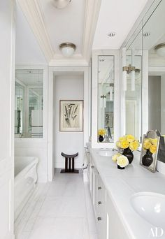 The master bath of Project Runway judge Nina Garcia's New York apartment features a ceiling light by Urban Archaeology; the sconces and tub are by Waterworks. The home was renovated and decorated by Carlos Aparicio of Aparicio + Assoc.