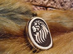 """Pendant """"lion"""" made of natural materials. A pattern in tribal style. The bone of cow, the base of the tree maple, accessories."""