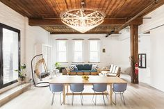 Dining space with modern chairs, wood table, and gorgeous chandelier