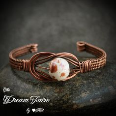 Porcelain and Wire Woven Copper Cuff: A brown spotted porcelain bead sits within a copper love knot in this open cuff bracelet.