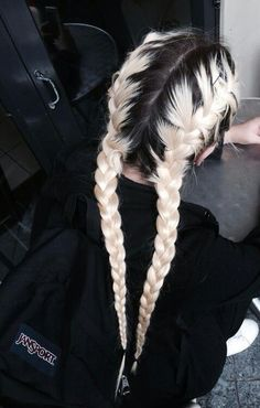 Long bleached blond hair. Two braids. Outgrowth