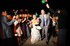 bride and groom exit while guests wave American and Brazilian Flags.  Red Pine Lodge, The Canyons Resort, Park City Utah.  Park City wedding.  loganwalkerphoto.com