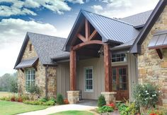 Large country style home featuring stone exterior, cedar beams over the entry space and metal roofing ... from Trent Williams Construction in Tyler, Texas