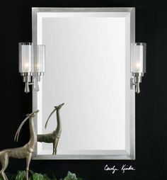 "Plated brushed nickel frame with two side arm lights that pivot left and right. Each light holds a 25 watt max candelabra bulb that is diffused by a frosted glass sleeve. Hard wire only. Mirror has a generous 1 1/4"" bevel."