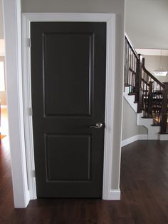 Breathtaking Single Woods Black Interior Doors With White Wall Color Painting And Mesmerizing Wooden Stair Case Also Great Rustic Wooden Flooring Installations For Inspiring Modern Living Room Decor Ideas