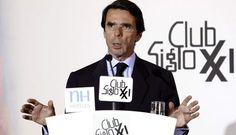 Spain's awful Ex-President José María Aznar spreading crap next to an ugly and unreadable logo.