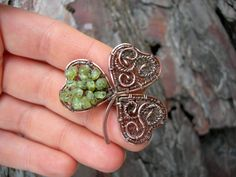 Wirewrapped copper brooch made ​​in the form of cloverleaf and decorated with raw chrysolite crystal beads. To give the brooch more rich and enchanted view it has been oxidized and polished. Copper lacquered by special varnish. Just do not scratch the surface and the metal does not get dark so fast.  Size 4 х 4см  ************************************************************************************** Copper is very soft metal. Avoid the mechanical affecting your jewelry.  Jewelry will be…