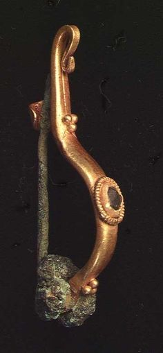 A ROMAN GOLD FIBULA, ca. 1st-3rd century AD. The solid gold fibula complete with granulation and blue glass inlay in ribbed wire setting with original pin.