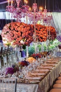Vibrant amethyst chandeliers hover over glamorous rose pomanders perched on crystal stands.
