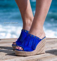 CUÑAS SAMARA AZUL Seguirán siendo uno de los modelos estrellas de la primavera-verano. Los mules son los zuecos que han vestido nuestros pies años atrás y seguirán hacéndolo. De esparto, con cuña, flecos y tachuelas: una combinación irresistible. Siroco Mojacar #sandals #sandalias #shoes #zapatos #moda #tendencias #styles  WEB: https://www.indalas.com