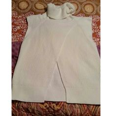 Banana Republic sleeveless chunky knit turtleneck Gorgeous ivory sleeveless turtleneck sweater in a soft cotton blend.  Split front, longer length.  Excellent condition no stains , piling or snags. Size xs but is a generous fit -can definitely fit a small or 4/6 Banana Republic Sweaters