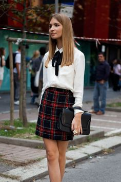 A tartan skirt with a white blouse shirt and neck tie. Back-to-school work outfit.
