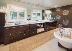 A stunning vanity draws you into this contemporary master bathroom. Spanning from wall to wall, the double vanity overlooks the backyard. Airy Roman shades offer privacy when needed.