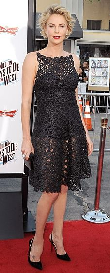 Charlize Theron wears a Christian Dior lace dress and bold red lips to the premiere of A Million Ways to Die