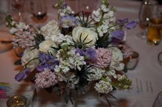 CENTERS A silver resin revere bowl filled with flowers to include white stock, white roses, light pink stock, blue thistle, lavender sweet pea and scabiosa. Touches of eucalyptus and sage throughout and spilling over the edges. From Shelly at http://theflower.biz/