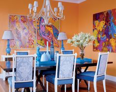 In the dining room, a David Iatesta  chandelier, custom-made table by Casa Woodworking, and lacquer chairs by Artistic Frame; paintings by Jeremy Stenger and a photograph by Irene Mamiye  are displayed on walls painted in Benjamin Moore's Calypso Orange.   - ELLEDecor.com