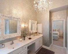 A #chandelier, wallcovering, and ornate mirrors over the sinks make for a gorgeous #glam #bathroom #design.