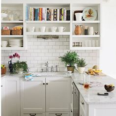 Gorgeous white kitchen with a grey marble counter top and a white tiled backsplash.
