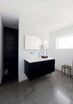 black vanity, shower, white wash walls, gray flooring