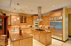 A kitchen with natural wood cabinetry, rich granite countertops, and a working island. What do you think of the layout?
