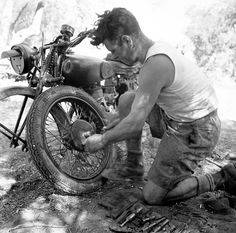 Private F. Jones of The Royal Canadian Regiment repairing his motorcycle near Militello, Italy, August 18, 1943