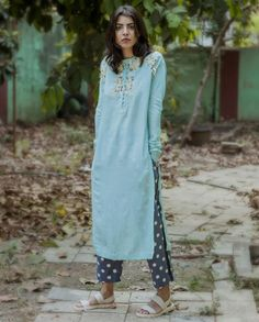 Aqua blue full sleeves tunic with floral applique and fringe detailing adorning the yoke. Round neckline with loop button placket. Wash Care: Dry clean onlyPant worn by the model is only for styling purposeDiscmailer: This garment is a relaxed fit silhouette.