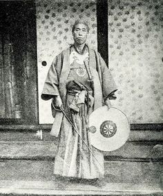 Samurai holding muchi (whip) and jingasa (war hat). Attributed to John Thomas Gulick (1832-1923) , 'Two sworded Officer Japan,' albumen-print stereoview published by the P.F. Weil studio in c.1870 and reproduced from an earlier 1862-63 negative or print.