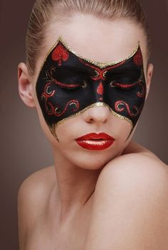 "Artistic black and red masquerade make-up mask with gold glitter and red crystal accents. ""The Mask"" by Magdalena."