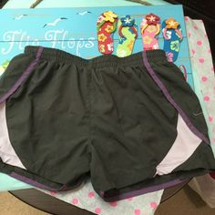 NIKE running Short with under panty, size medium Like new Nike running shorts with inside tie to adjust waist, also small inner pocket for keys inside. Size medium ,color gray with plum trim. Nike Shorts Skorts
