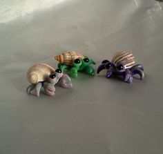 These three little amigos will brighten up your day. They are handmade miniature polymer clay hermit crabs in pastel pink, purple, and green. Each crab has their own marbling of colors, so they are truly OOAK. They have little black glass beads for eyes. They love hanging out in fairy gardens, house plants, terrariums, floral arrangements, indoor water fountains, your desk, your best friends head....Anywhere!. They are approximately 1 1/4 across and 1/2 tall. Each has their own gen...