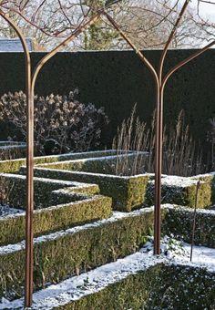 White Garden at Sissinghurst Castle Garden demonstrating how important topiary is for structure in the garden in Winter.