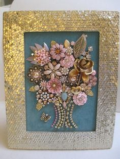 This piece is fabulous! Measuring approximately 9 x 7 inches from the outside edges of the detailed gold tabletop frame with easel backing. Soft blue velvet embellished with multiple vintage and contemporary elements make up this lovely bouquet. Perfect gift or for your own home. The