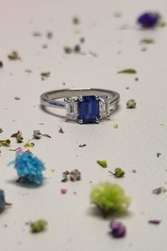 The trio of gemstones in this sapphire and diamond ring are all emerald-cut. The deep blue sapphire weighs 0.94ct and the two diamonds weigh a total of 0.50ct. #BlueSapphireRing #BlueSapphire #HattonGarden #TrilogyRing #ThreeStoneRing Three Stone Engagement Rings, Three Stone Rings, Designer Engagement Rings, Diamond Engagement Rings, Hatton Garden, Blue Sapphire Rings, Emerald Cut, Ring Designs, Two By Two